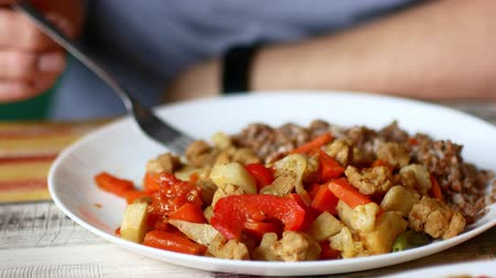 soy : The man is eating stewed vegetables. Vegan food.