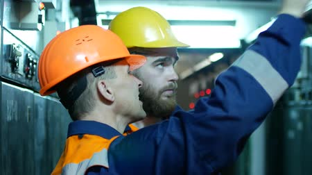 examining : Two workers talking in a factory. Stock Footage