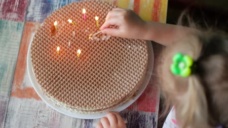 az yağlı : A little girl lights candles on a homemade cake. The concept of autonomy