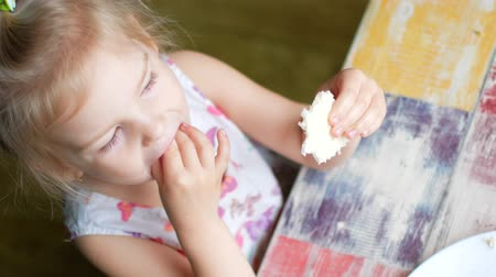 diyabet : A little girl is eating waffles. She licks her fingers Stok Video