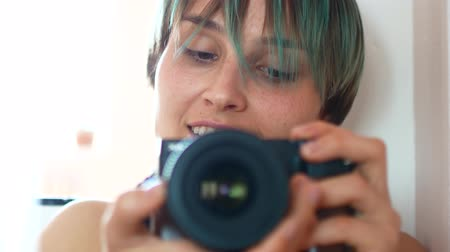 film camera : A young woman takes herself to the camera through a mirror.