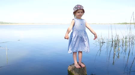 tuskó : Young girl in dress standing with open arms at lakeside. Stock mozgókép