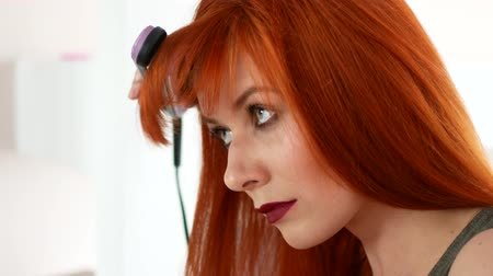 žehlení : Red-haired woman balancing her hair with an iron before the mirror.
