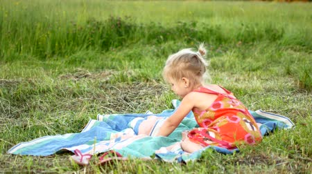 fonat : A little blonde is sitting on a plaid on the grass.