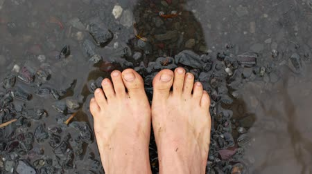 andar : Walking barefoot through a puddle.