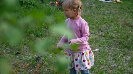 yalınayak : A preschool girl with a tourist saw in her hands tries to cut wood in the forest. Stok Video
