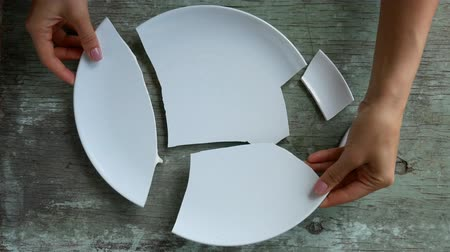 shattered : pile of broken white plates on rotating plate. Fixing a broken one