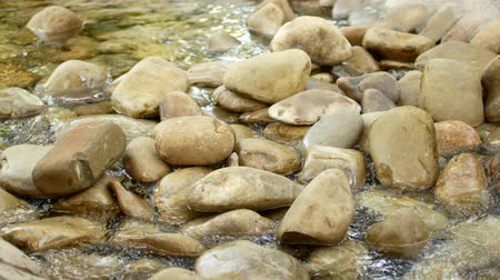 identical : water flows around balanced stones in flowing river. Stock Footage