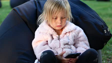 Little girl watching cartoons in phone.