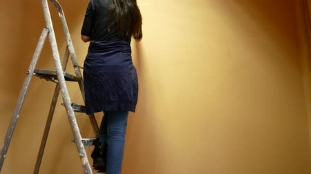 мольберт : Girl artist paints a wall standing on a ladder.