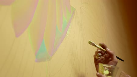 Young brunette paints a picture on the wall, profile.