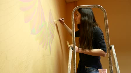 manichino : Girl artist paints a wall standing on a ladder.