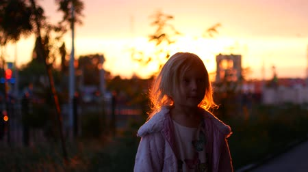 desgrenhado : A little blonde girl stands in the rays of the setting sun.