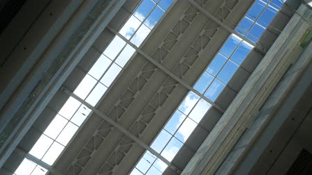 shot of glass ceiling of the shopping center on a background of time-lapse light of the sun rays on a blue sky. Dostupné videozáznamy