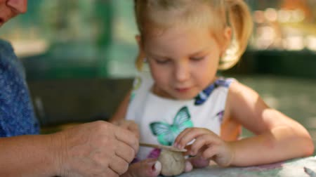 plastelíny : A little girl sculpts clay figurines with the help of her grandmother.