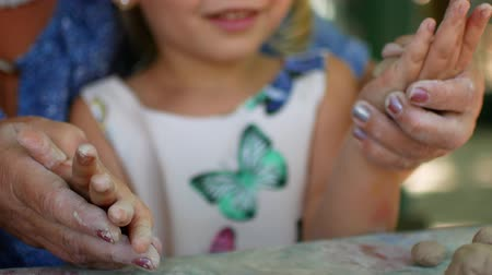 moldagem : A little girl sculpts clay figurines with the help of her grandmother.