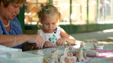 çabaları : A little girl sculpts clay figurines with the help of her grandmother.