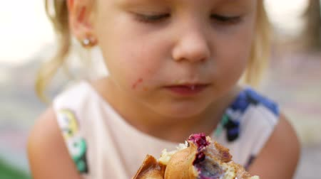 мотылек : A small wonderful girl is eating waffles with fruit and ice cream. The summer cafe. Стоковые видеозаписи