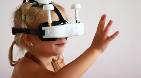 insight : little girl wearing virtual reality glasses, playing video games Cheerful smiling, looking in VR glasses and hand gesture