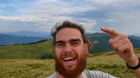 A man does selfie in the mountains. Joyous video, turn in a circle. Dostupné videozáznamy