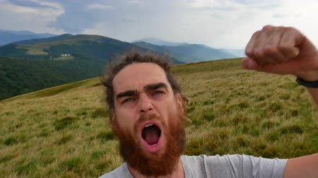 A man does selfie in the mountains. Joyous video, turn in a circle. 影像素材
