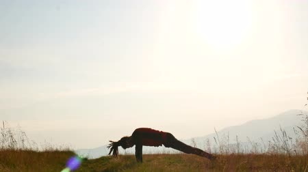 A man with dreadlocks is doing yoga at dawn. Mountains of Carpathians, Ukraine.