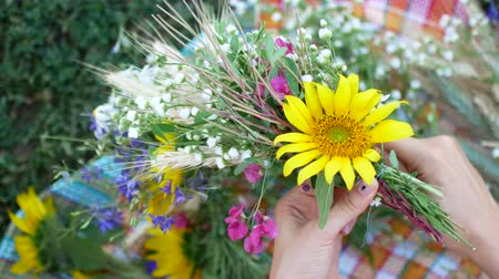 Female hands make a wreath of summer wildflowers.