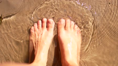 stopa : Barefooted female legs on the beach. Wideo