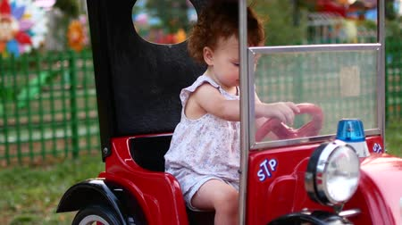 szórakoztatás : Child girl and rides an electric car in the park for entertainment. Attractions for children. Playground.