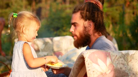 huevos revueltos : A little girl is feeding her dad with a spoon. Summer evening in the village