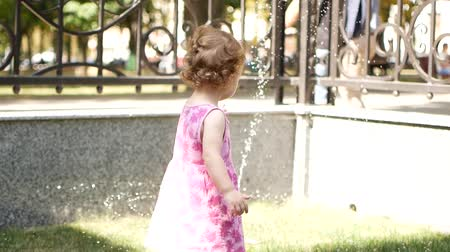 megpróbál : The Toddler Girl is trying to handle the water from the fountain. Stock mozgókép