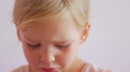 sulky : Offended little girl on a white background. Sad portrait of blonde child.