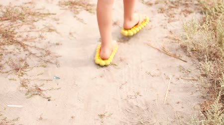 тапочка : Childrens legs wearing rubber flip-flops on the beach
