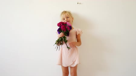first class : Young dancer posing with a bouquet of flowers. Happy little ballerina