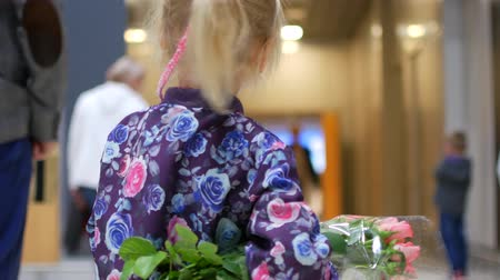 desgrenhado : Little girl with a bouquet of roses in the airport lounge. Stock Footage
