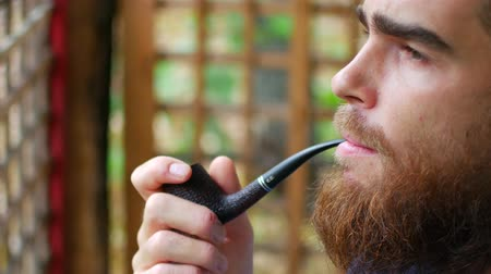 клетчатый : Close up of attractive man with beard smoking on the beach. Outside. Portrait.