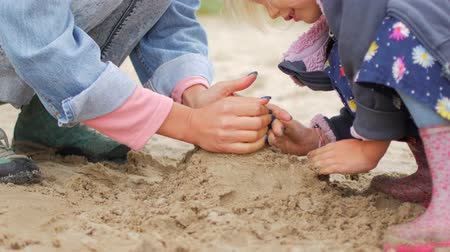 osm : Children playing sand on the beach. Mom helps her daughter to build a castle. Autumn day.