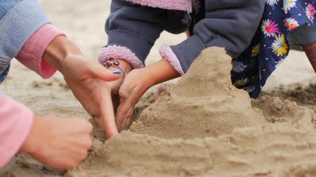 patting : Children playing sand on the beach. Mom helps her daughter to build a castle. Autumn day.