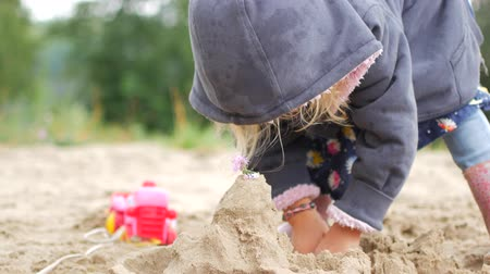 восемь : Children playing sand on the beach. Little girl builds sand castle by himself on the beach Стоковые видеозаписи