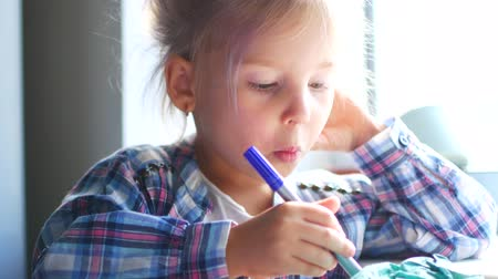 sundurma : Cute Little Girl Sits at Her Table and Draws with Crayons