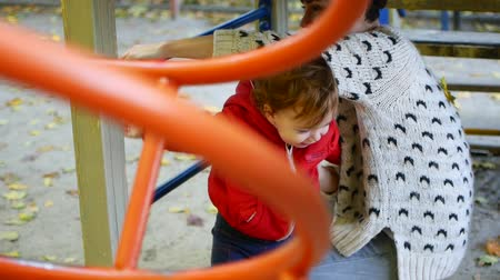 дочь : Mom and baby are playing on the playground in the warm autumn. Стоковые видеозаписи