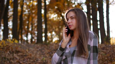 factor : Girl in yellow forest. Woman talking on the phone in the autumn forest Stock Footage