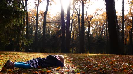 insult : Little girl is lying on her stomach in the autumn forest. Insult, hysteria.