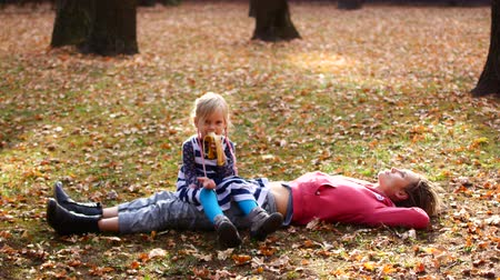 olhando para baixo : Beautiful mom and cute kid lying on the grass in autumn park. Daughter sits on mom and eats banana, mom looks to the sky.