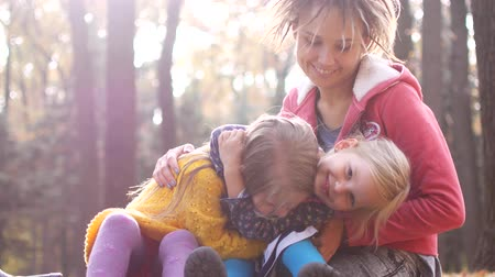 сестры : Mom with little girls on a picnic in the autumn forest.