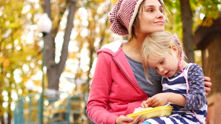 puericultura : Mom and daughter have lunch in the park on an autumn afternoon. Love, family, food. Stock Footage