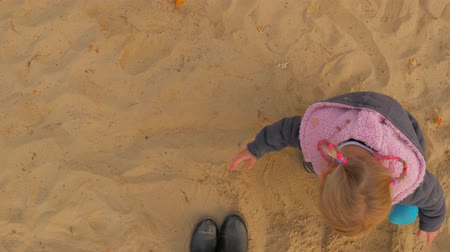 sandpit : The Girl Is Playing In The Sandbox. The Sandbox, A Little Blonde Sculpts Figurines From Sand