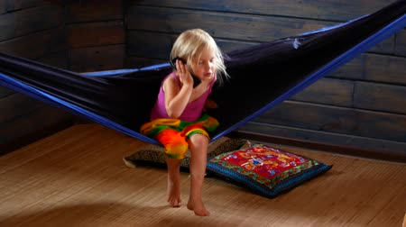 cosiness : Little girl swinging in a hammock and talking on the phone. Stock Footage