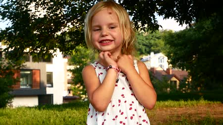 risonho : Closeup portrait of beautiful cute caucasian little girl smiling and laughing while looking at camera. Real time full hd video footage