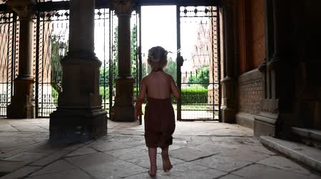valoun : A little girl runs through the arch of an old castle.
